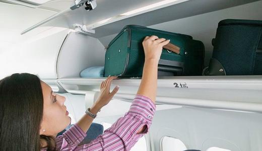 Женщина выкладывает ручную кладь на полку самолета